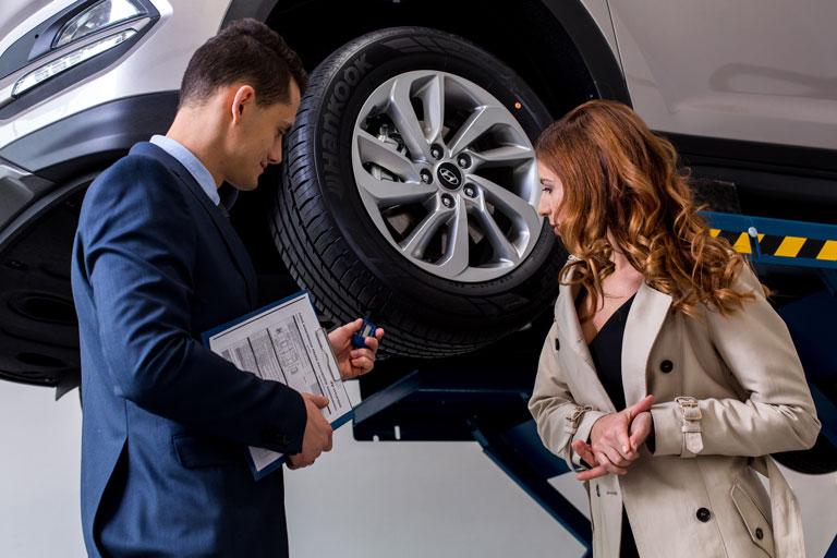 kobieta i mężczyzna, stoją przed autem, on mierzy bieżnik w oponie, ona podziwia